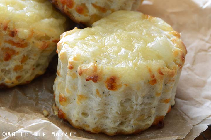 Close Up of Savory Cheese and Thyme Scone on Parchment Paper