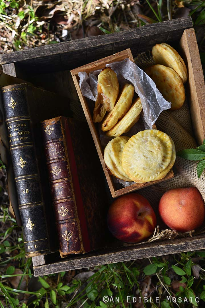 Peach Hand Pies with Fresh Peaches and Vintage Books in Wooden Crate Outside on Grass