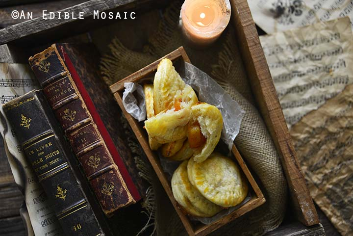 Peach Hand Pies in Dark Wooden Box with Old Books and Candle