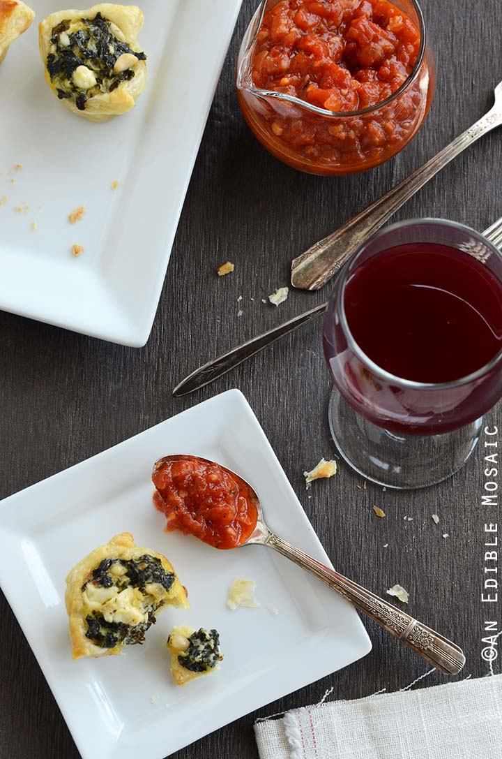 Spanakopita Puff Pastry Bites on White Plate with Tomato Sauce and Wine Glass