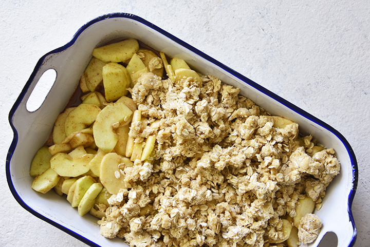 Spreading Crumble Topping on Apple Filling in Baking Pan