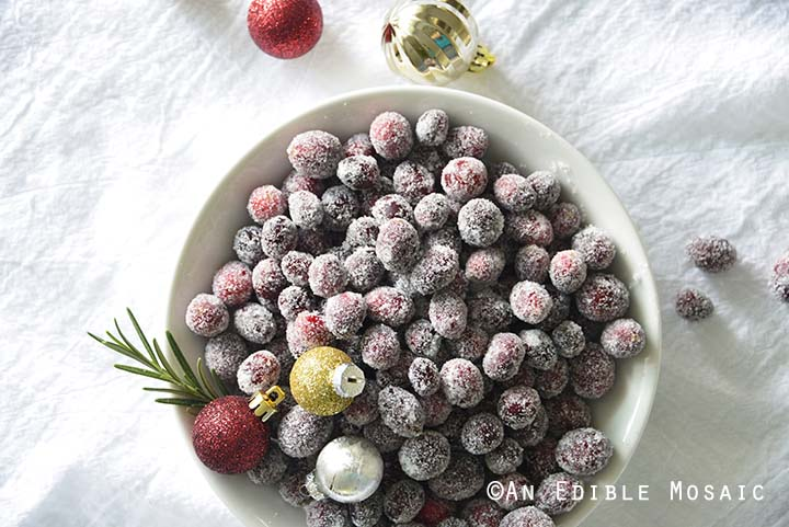 Sugared Cranberries with Christmas Ornaments and Rosemary in White Bowl