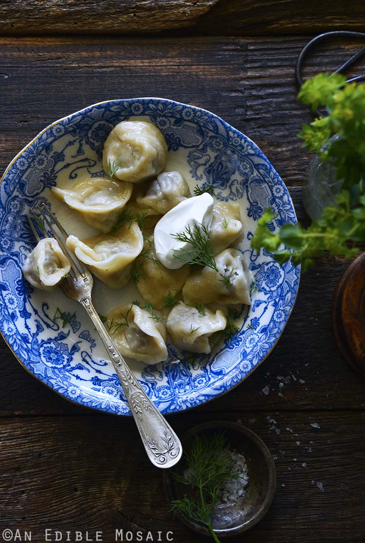 Pelmeni Recipe in Blue and White Bowl on Dark Wood Table