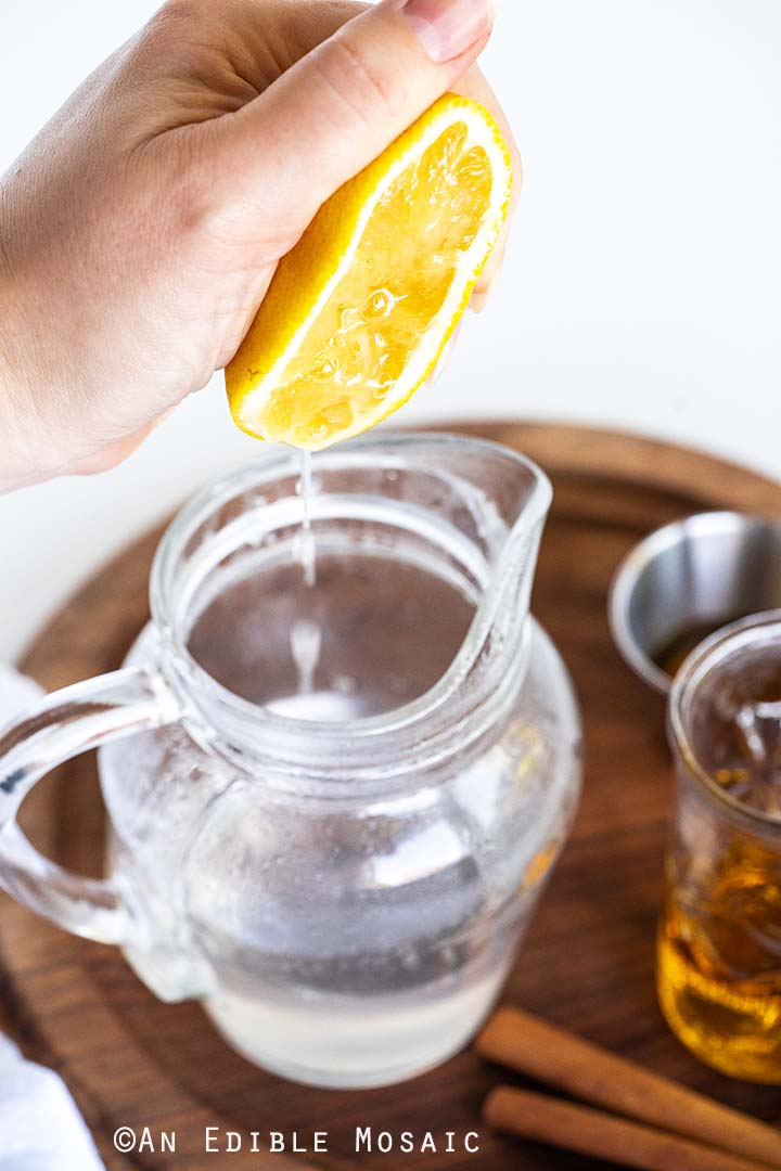 Squeezing Lemon Into Glass Pitcher with Water